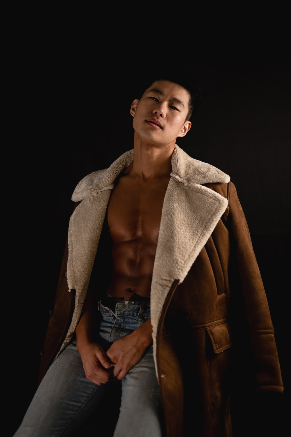 man in blue denim jeans with brown leather coat draped over shoulders
