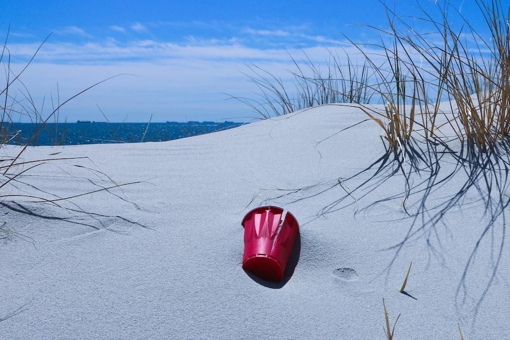 red plastic bucket on gray sand