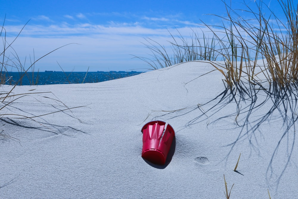 red plastic bucket on gray sand
