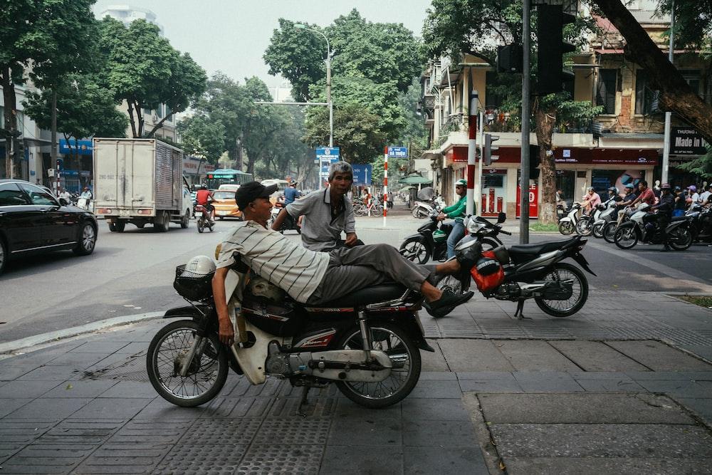 man lying on motorcycle during daytime