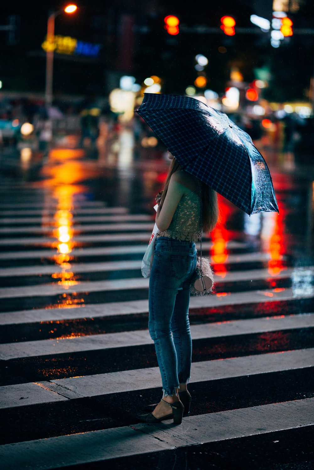 woman in blue jeans standing at the pedestrian lane holding umbrella