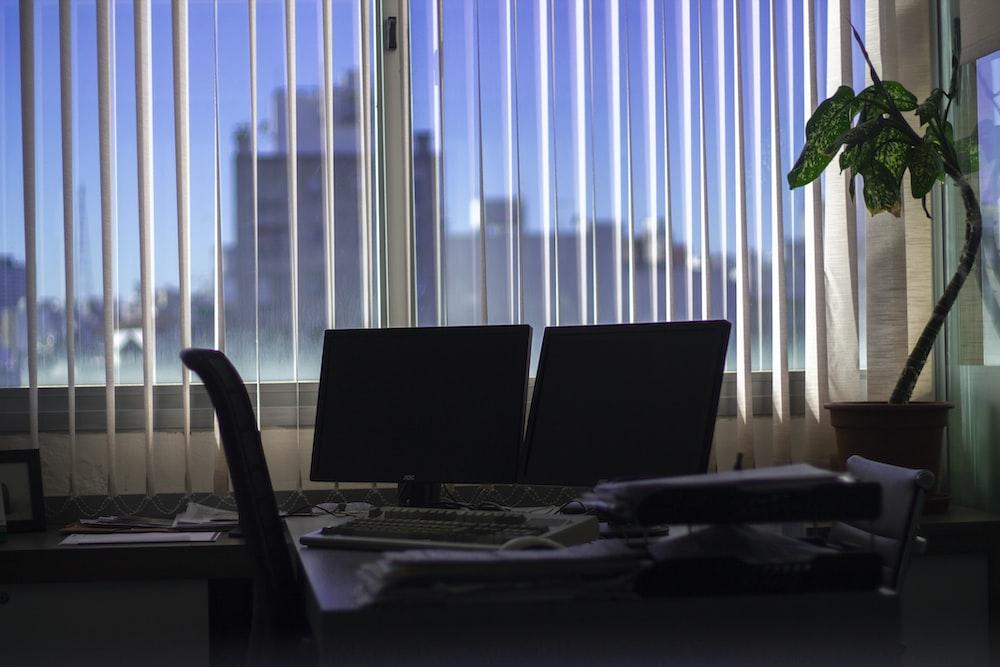 two black flat screen monitors on desk near window