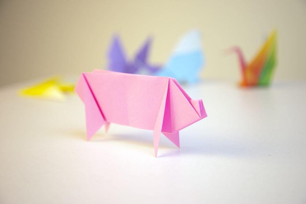pink origami in front of other color origamis