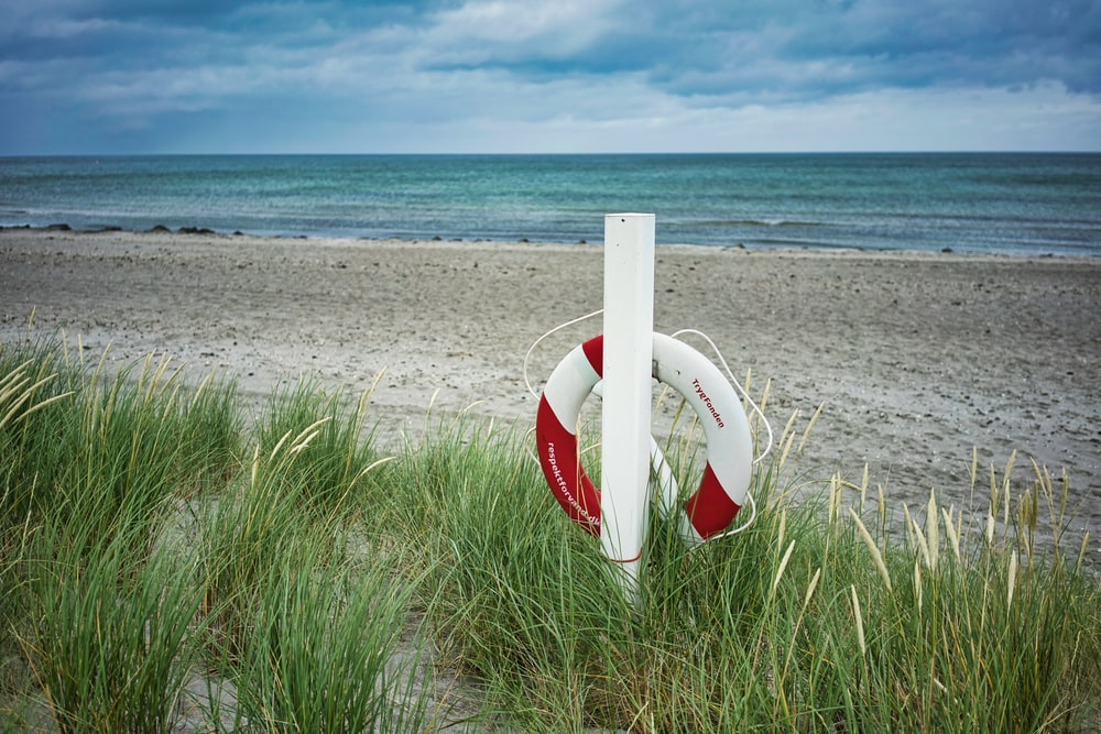 life saver hung on post on shore during day