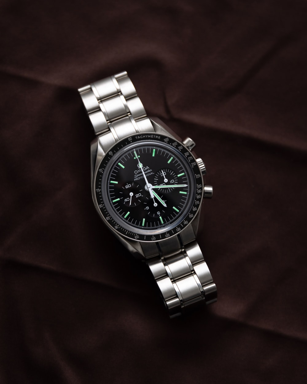 shallow focus photo of round silver-colored chronograph watch with link bracelet