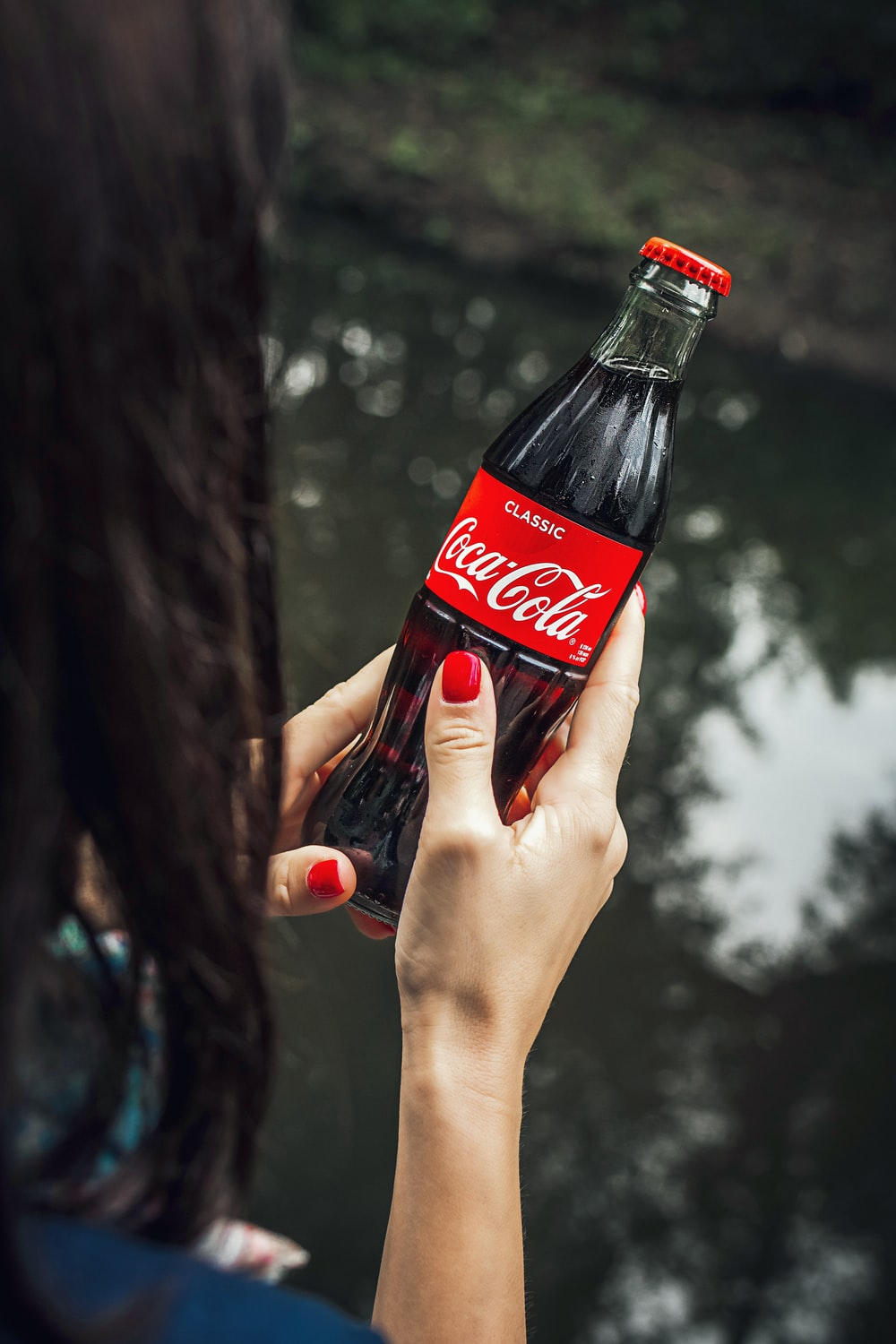 women holding a red Coca-Cola bottle during daytime