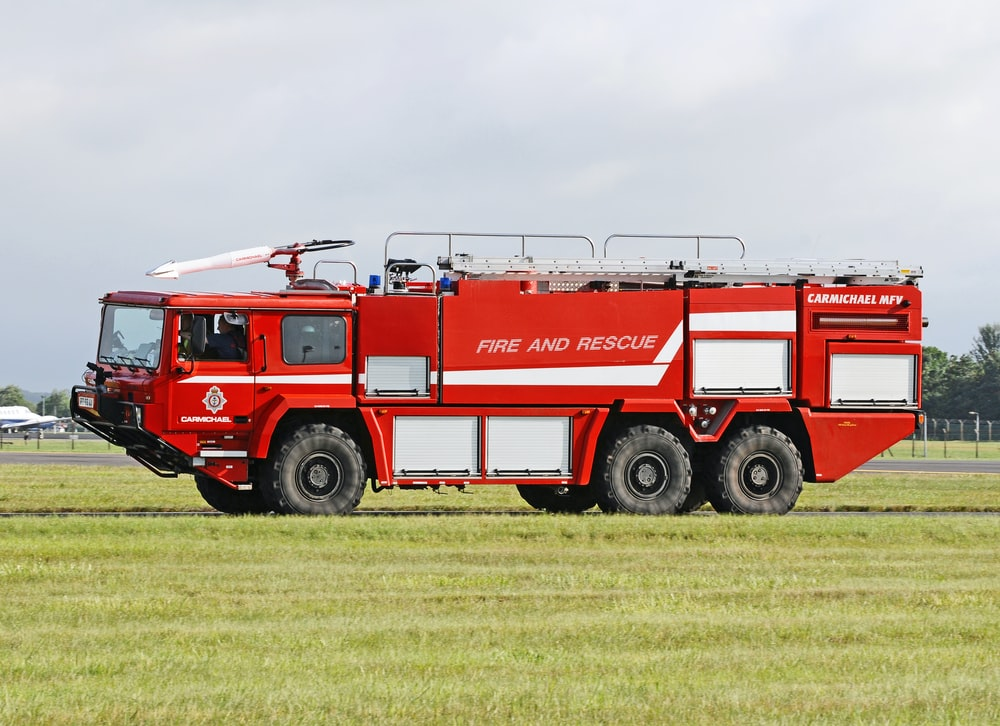 red and white fire engine on green grass field