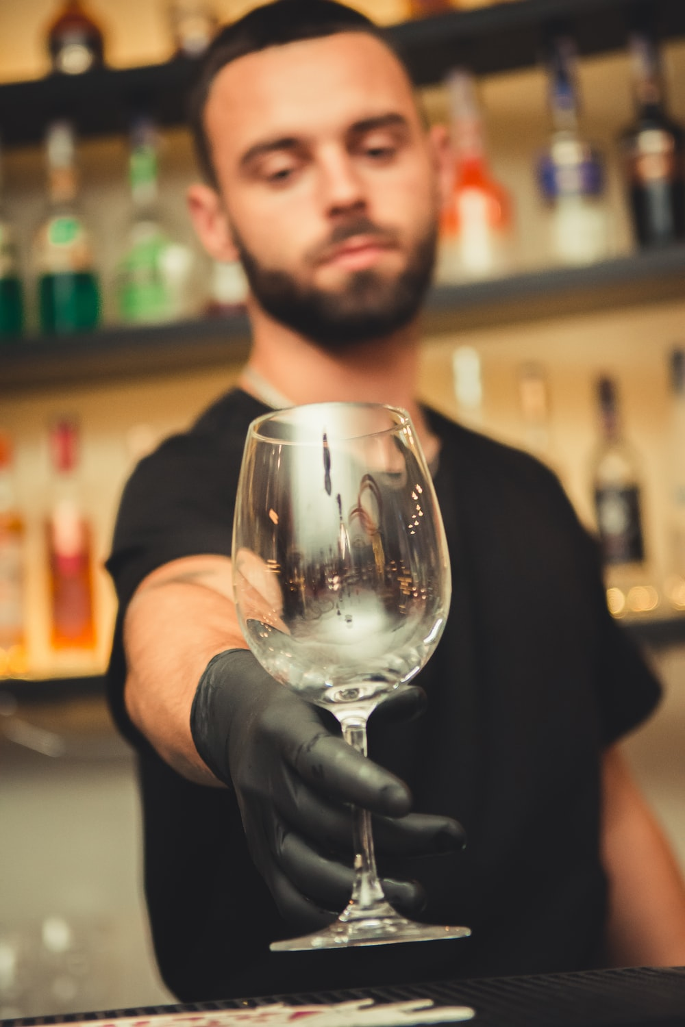 man holding empty clear glass wine goblet