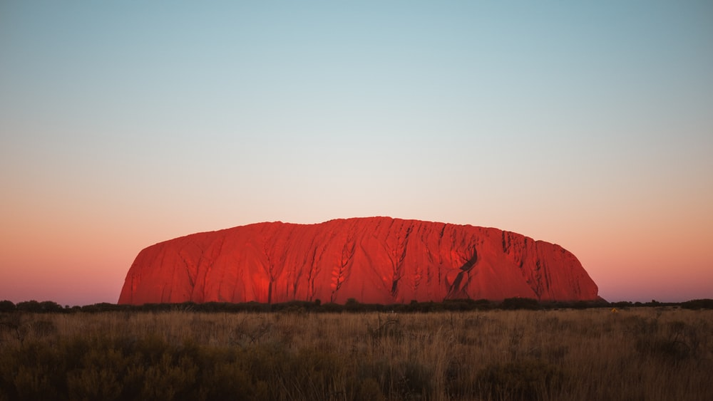 red mountain under blue sky at golden hour