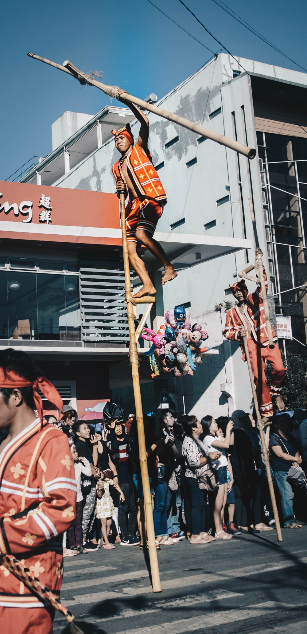 man in orange outfit standing on pole