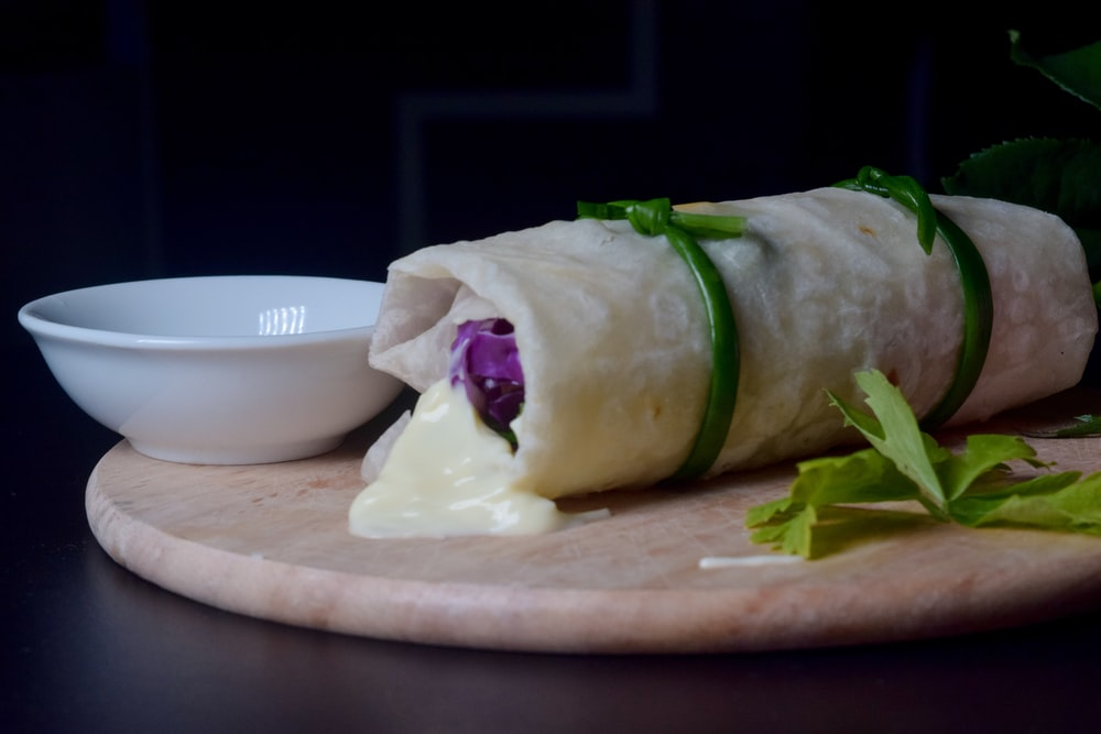wrapped food on brown wooden tray
