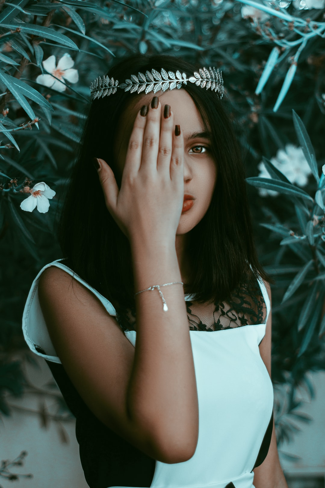Fine art fairy tale portrait of a gorgeous model  hiding her right eye with her hand.