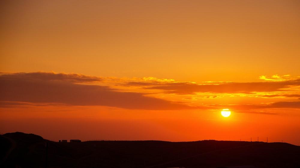 silhouette of mountain under orange skies