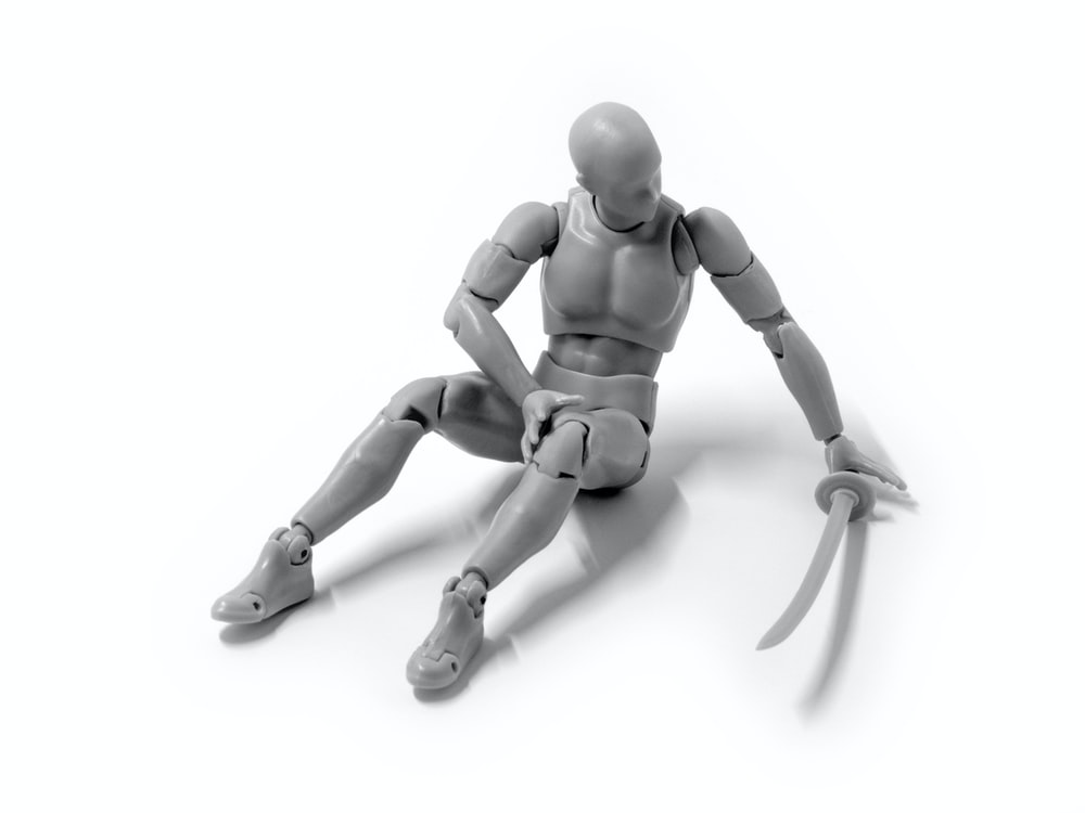 gray human model holding katana sitting