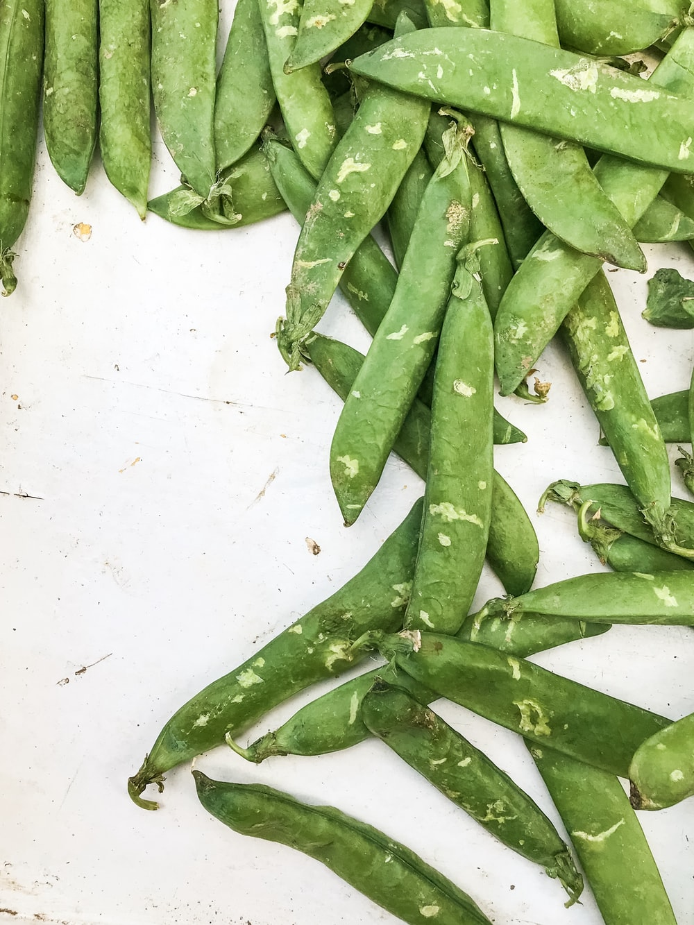 green beans on white surface