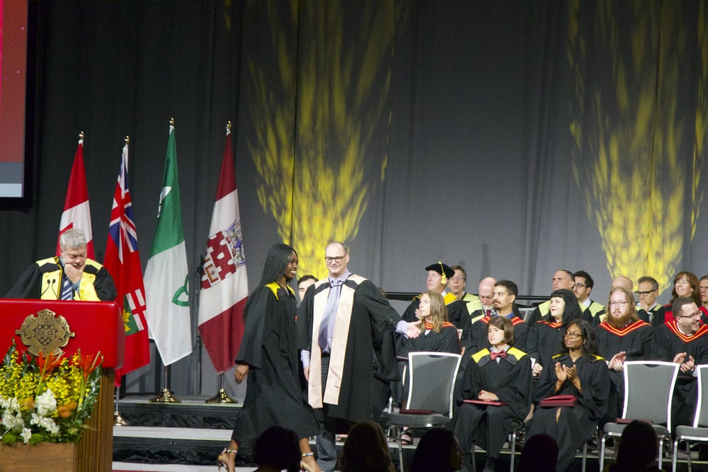 woman wearing black academic gown on stage