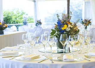 clear long-stem wine glasses on table near flower centerpiece on table
