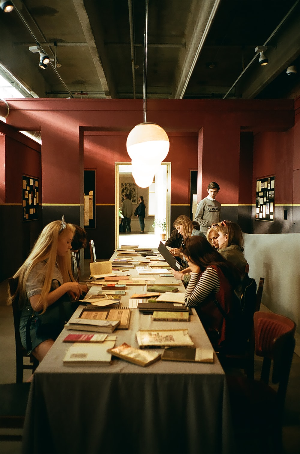 women sitting at table reading books