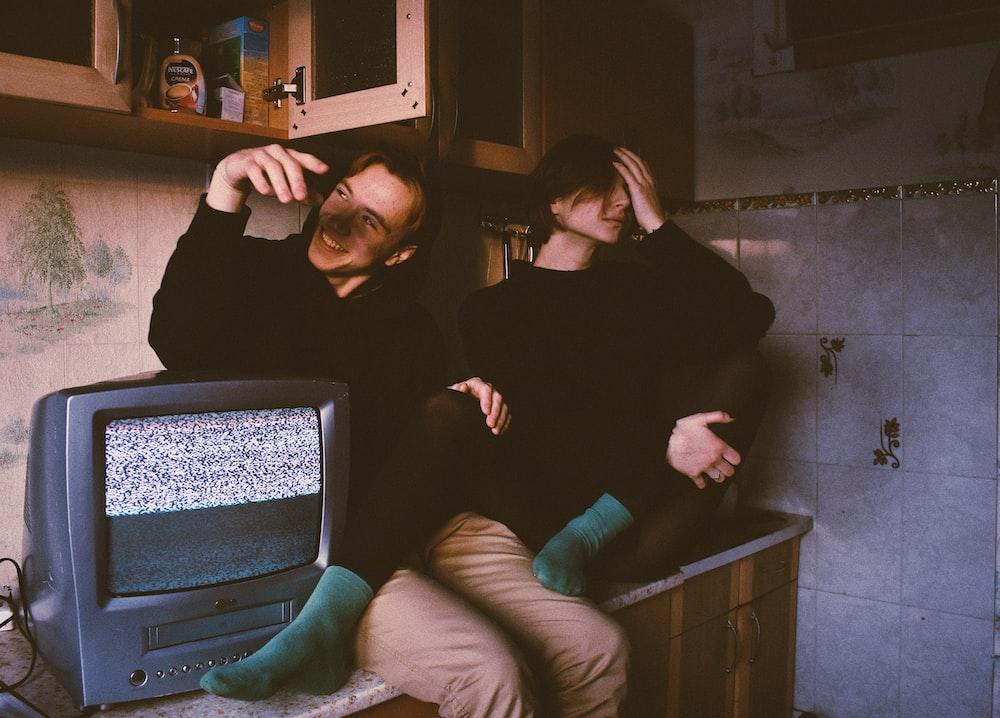 two men sitting beside CRT TV