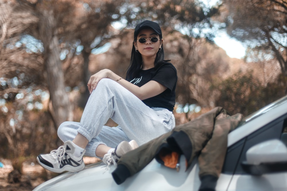 woman sitting on vehicle hood