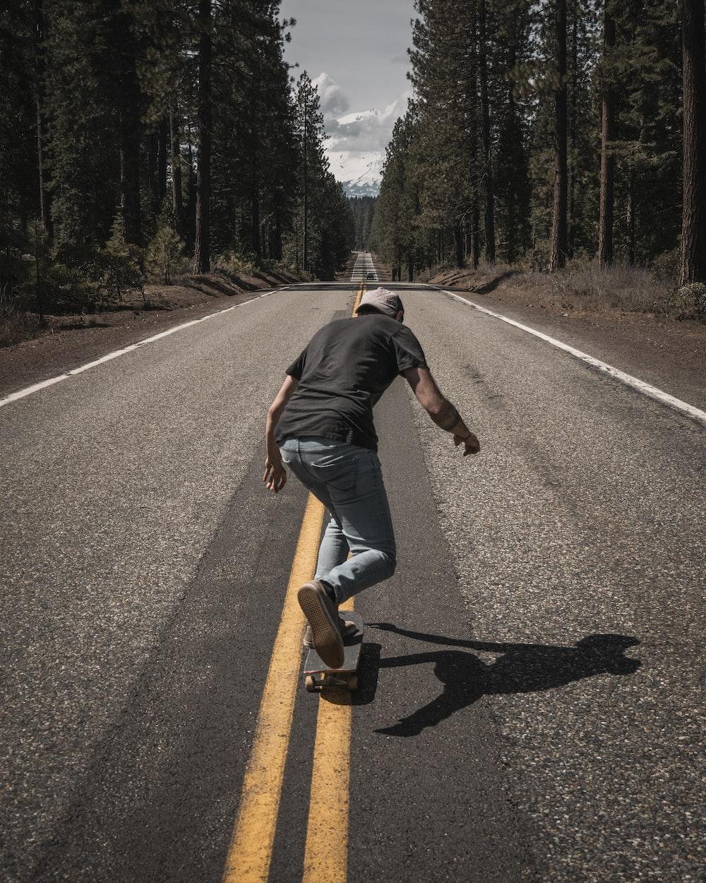 man playing skateboard on road during daytime