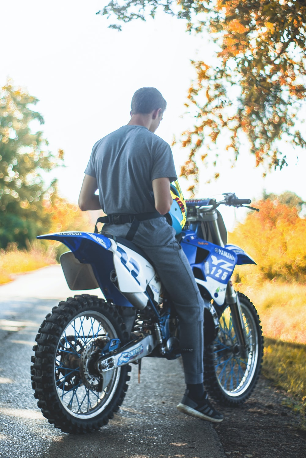man in grey t-shirt sitting on blue and white dirt bike