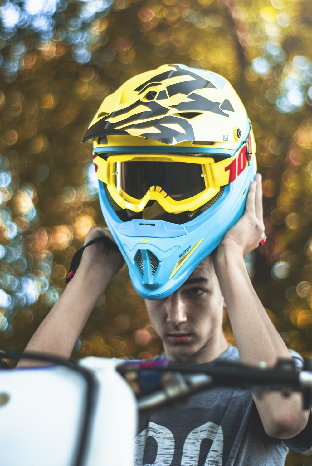 man holding yellow and blue motocross helmet