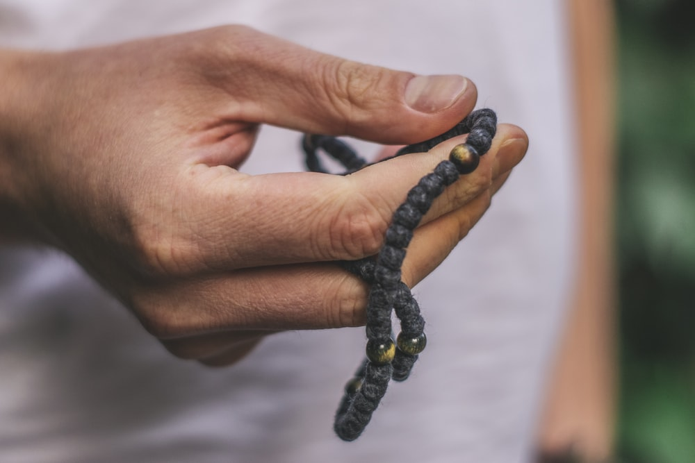 person holding black accessory