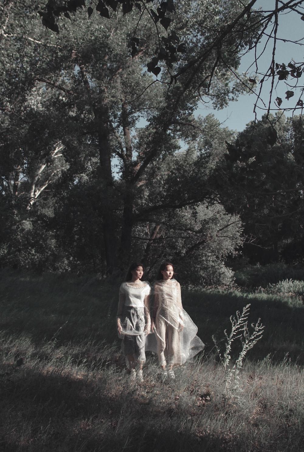 two women wearing white dress