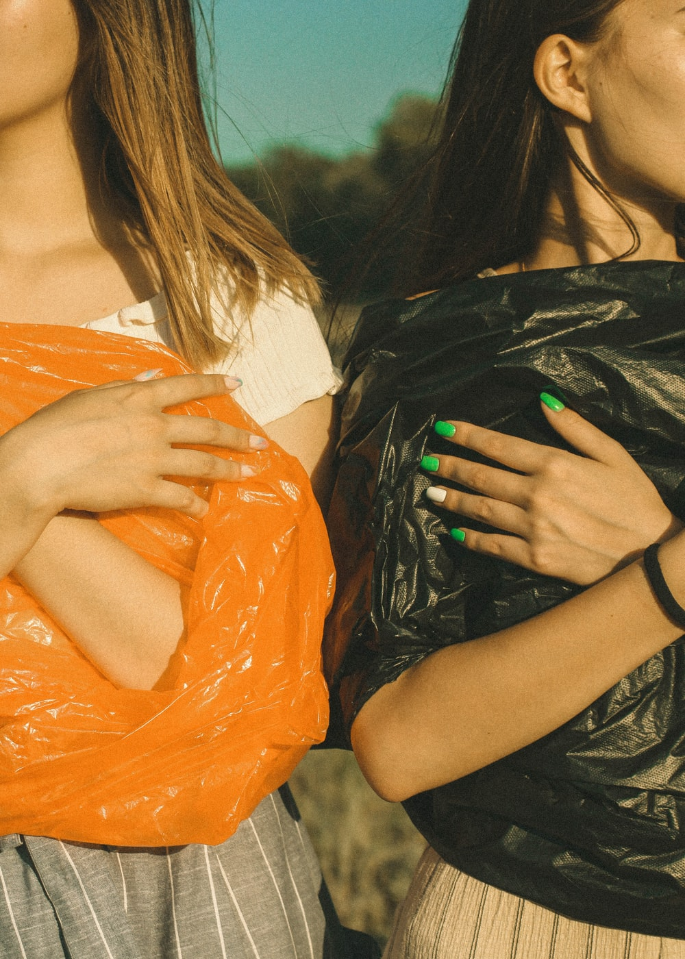 two women wearing black and orange plastic bags