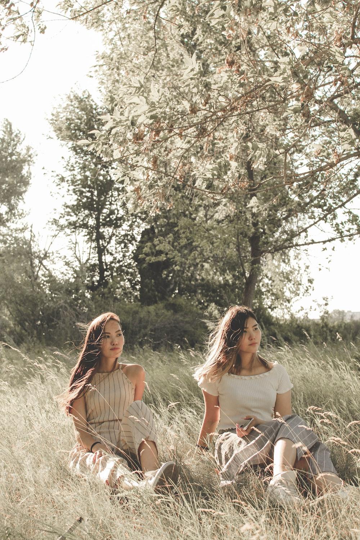 two women sitting on green grass field
