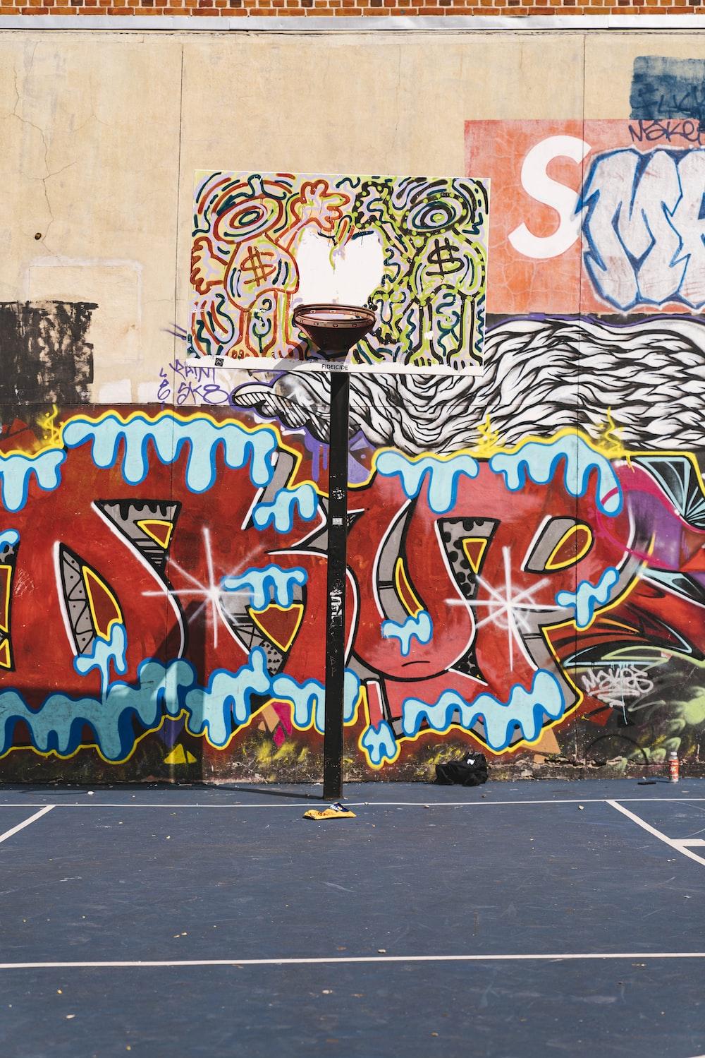 painted basketball hoop near graffiti wall