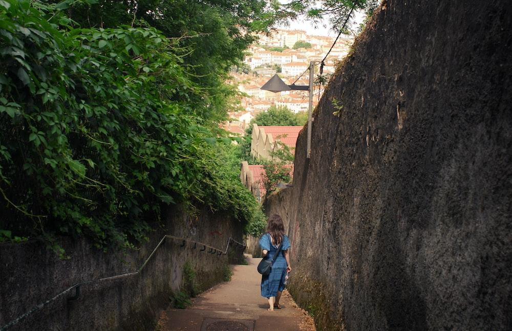 woman walking between wall and plant