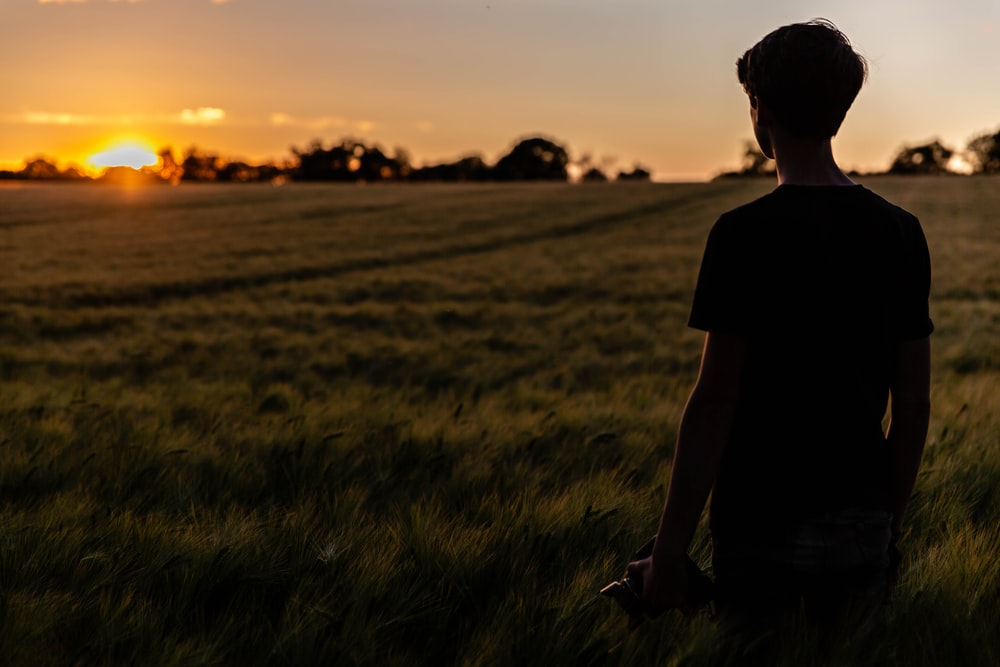 silhouette of person standing on green grass