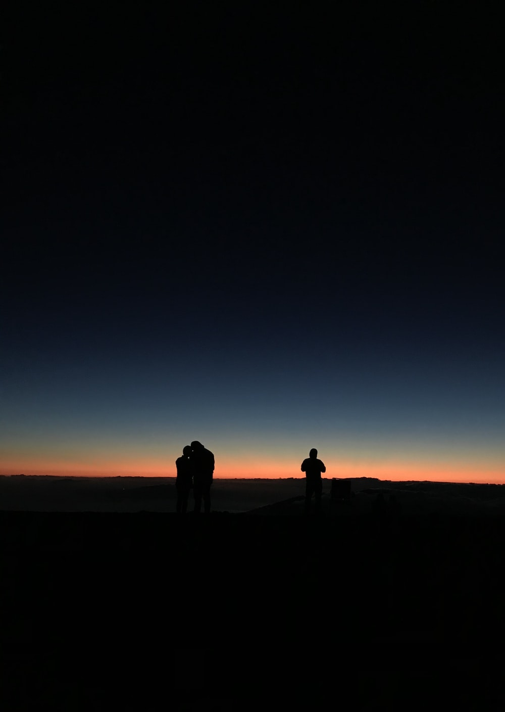 silhouette of 3 people at sunset