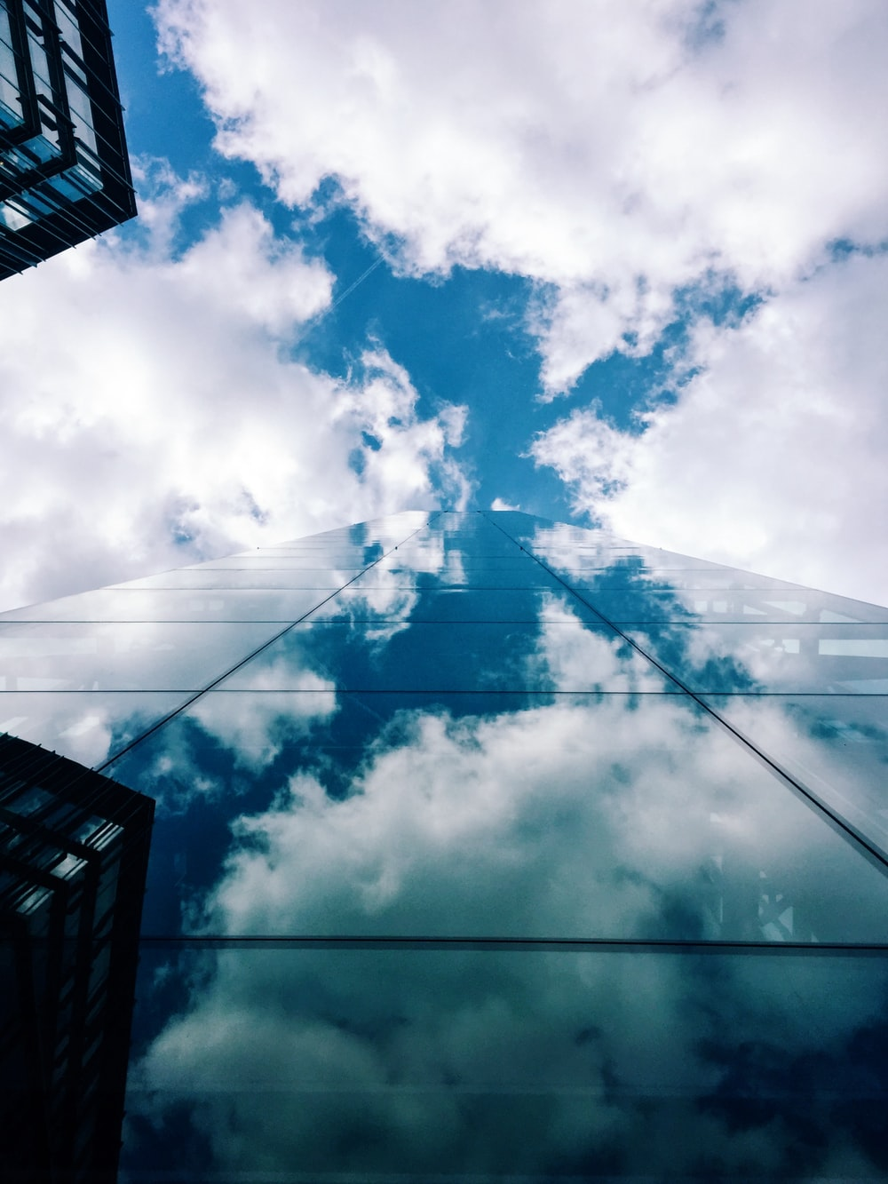 worm's-eye view of glass building across white clouds