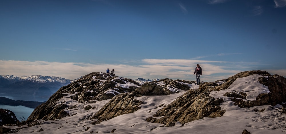 person standing on snow-capped mountain during daytime