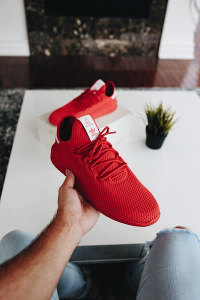 pair of red Adidas low-top shoes