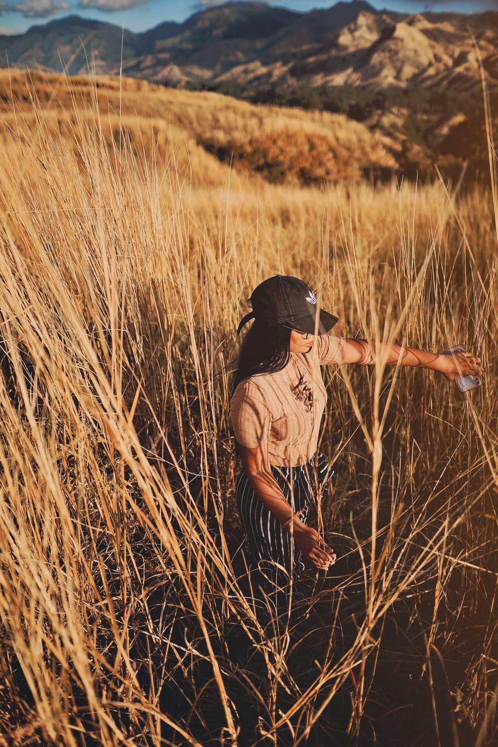 woman standing on brown grass field during daytime