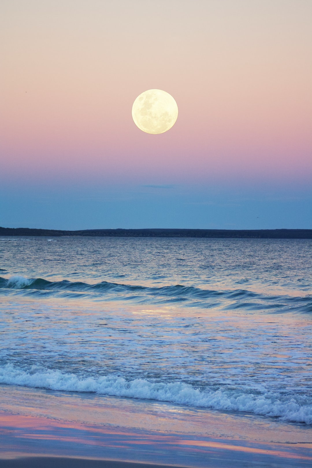 The nearly full moon rising over Jervis Bay, Australia, in blue hour as the last pink leaves the sky.  The famous white sand beaches and crystal clear water catch the light beautifully as it fades.  In this image I have increased saturation, contrast and the the moon to better capture the feeling of being there.