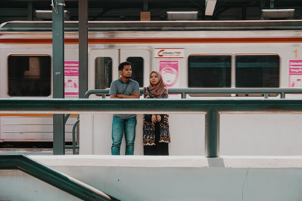 man and woman standing near train