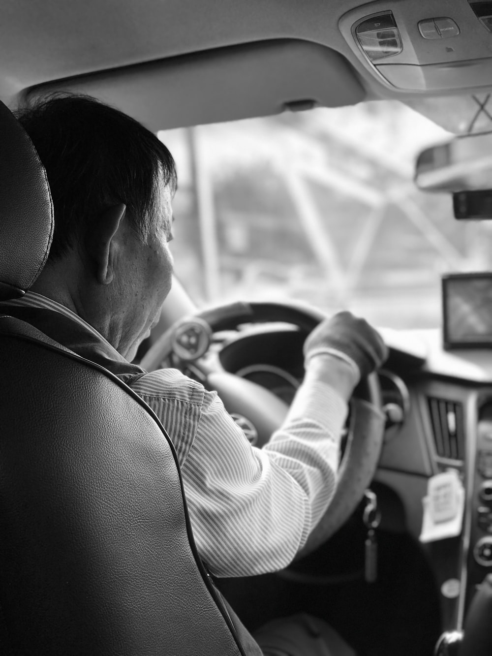 grayscale photography of man driving vehicle