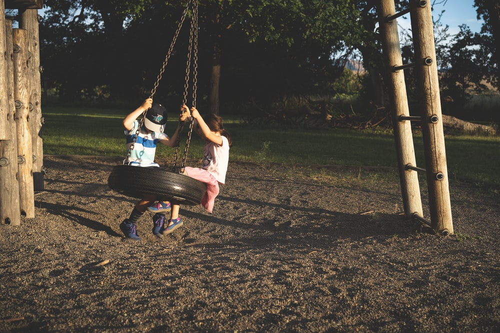 boy and kid on tire swing