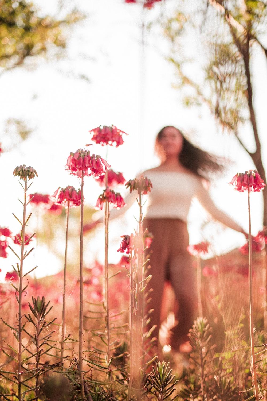 woman walking on red flower field