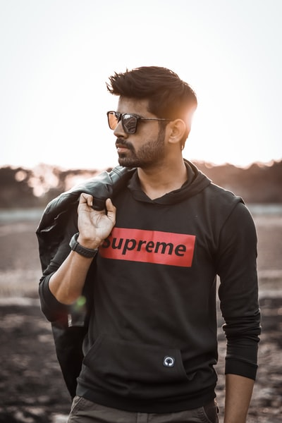 shallow focus photo of man in black Supreme pullover hoodie