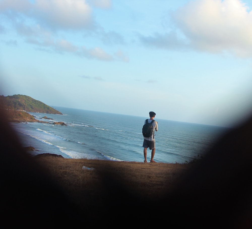 person in grey t-shirt standing at the shore