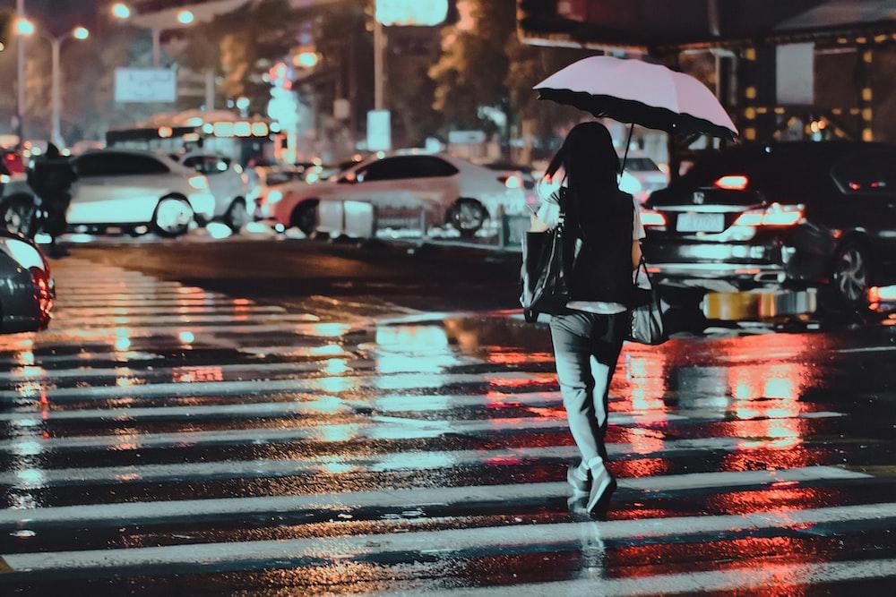 woman using umbrella crossing on pedestrian lane during nighttime