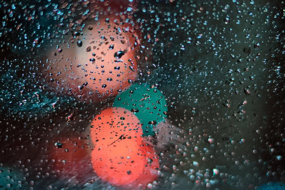 透明なガラス表面の水滴のボケ写真