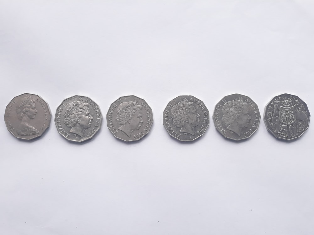 six silver-colored coins on white surface
