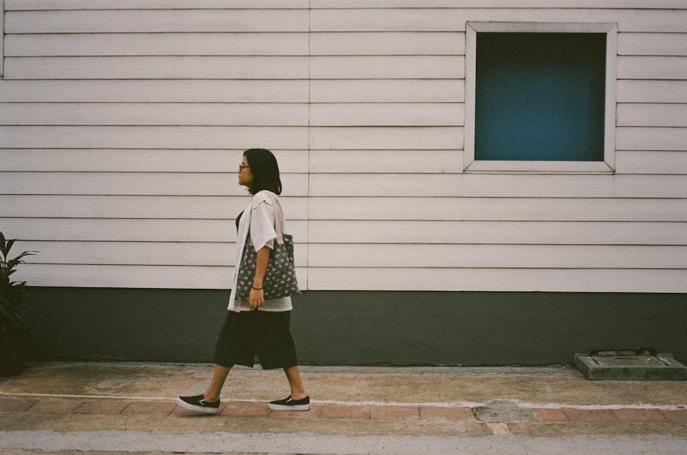 woman walking on pathway beside house